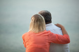 Waist Up Rear View of Unrecognizable Mature Couple with Arms Around Each Other Admiring Romantic Sunset Over Water