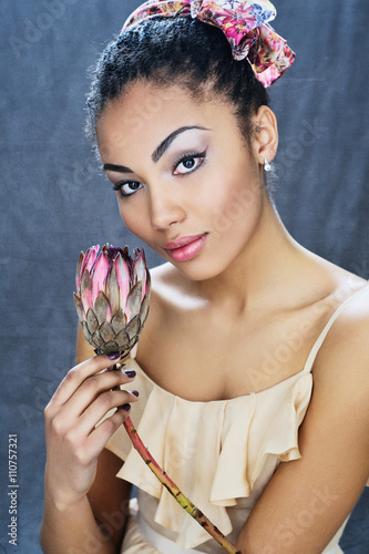 Poster Beautiful mixed race young girl holding African protea flower