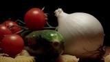 Onion zucchini cherry tomatoes pasta on wooden cutting board