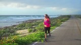 Healthy lifestyle,woman in sportswear jogging doing exercise on ocean coastal road early morning