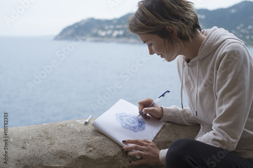 Young woman drawing a purple mandala pattern on a sketchpad with a pencil outdoo