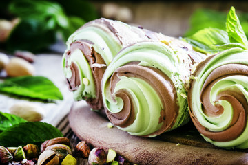 Green pistachio ice cream with chocolate and mint in cones, vint