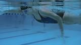 Underwater view of professional female swimmer performing front crawl in swimming pool