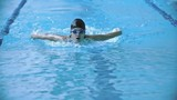 Professional sportswoman swimming butterfly stroke in pool in slow motion towards the camera