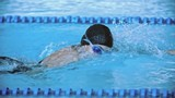 Side view of sportswoman wearing cap and goggles and swimming front crawl in pool in slow motion