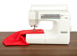 Sewing machine and red fabric isolated on white