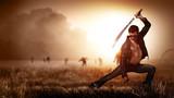 Männlicher Kämpfer mit Machete vor einem Feld voller Zombies