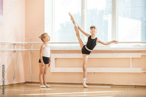 Little girl watching older ballet student practicing at barre © Andrey Bandurenko