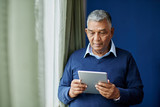 Pensive old man with digital tablet standing at window