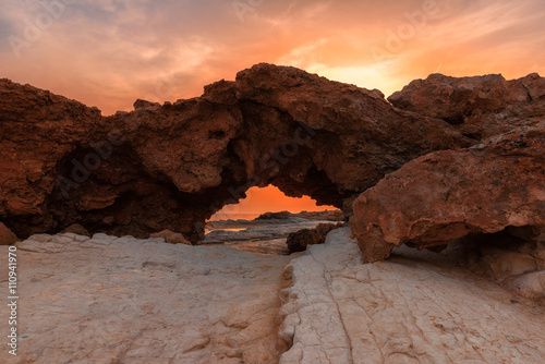 Natural Arch at sunset on Cyprus beach in Mediterranean sea