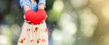 Girl presenting or giving big red heart on bokeh natural green background