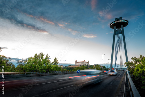 View on the Modern bridge with observation deck and restaurant called UFO and castle in Bratislava city at the sunset. Long exposure technique with motion of cars