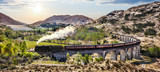Glenfinnan Railway Viaduct in Scotland with the Jacobite steam train against sunset over lake - 110968730