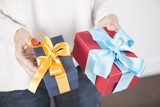woman blue jeans cream jersey with two gift boxes in both hands, blue yellow and red cyan, over white background