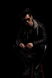 man in leather jacket and boots wearing sunglasses sitting