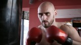 Male boxer in red boxing gloves training in gym with punching bag