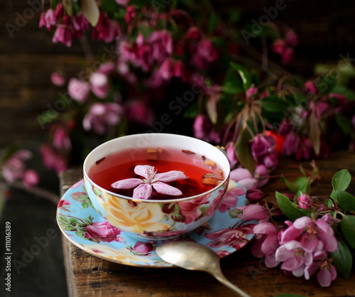 fruit tea in a cup and pink flowers on a wooden background © venge