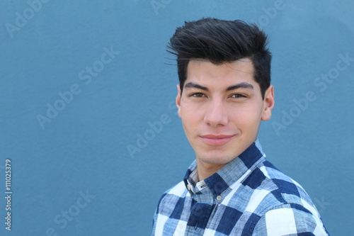 Handsome hispanic man with a perfect white smile isolated on a blue background w Poster