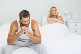 Upset couple ignoring each other after fight on bed