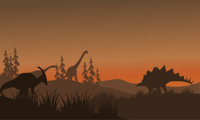 Silhouette oof many dinosaur in hills
