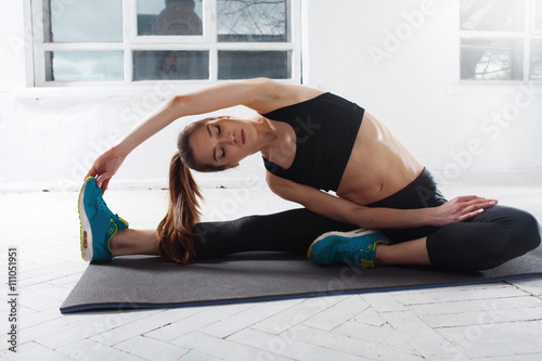 Fototapeta Beautiful slim brunette doing some stretching exercises in a gym