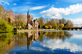 Minnewater lake panorama, reflection of gothic building Castle de la Faille, cloudy blue sky, Bruges, Belgium