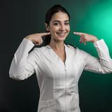 medico donna si indica le guance - sfondo verde