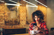 Detaily fotografie Young woman at cafe drinking coffee and using mobile phone
