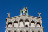 Blue Eyed Angel Atop an Ornate Church Facade