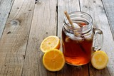 Mason jar glass of cold iced tea with lemon slices on a rustic wood background