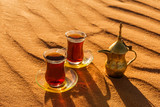 Arabic tea in traditional glasses and pot on desert at sunset - 111131332