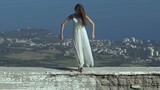 Slow motion shot of a young female standing on top of the high cliff above the city and sea, raising her hand up..