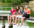 Gruppe Teenager lesen draußen ein Buch