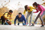 Group of friends doing push-ups at the park and making fun,smiling and laughing.Autumn season. - Fine Art prints