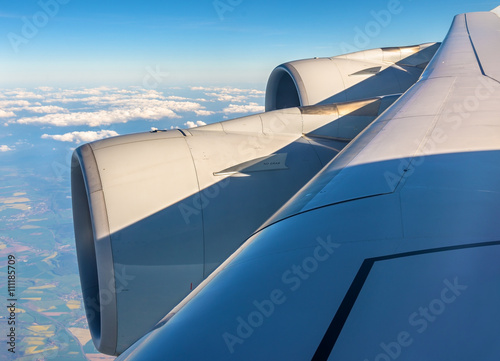 Wing with engines of Airbus A380 flying over clouds Poster
