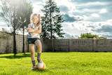 Little girl playing soccer in the garden and having fun.