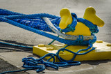 Heavy blue ropes of an ocean-going ship wrap around a yellow mooring bollard on a city pier in the harbor. - 111203576