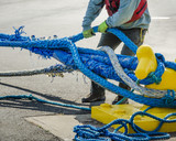 Dock worker pulls on heavy blue ropes of an ocean-going passenger ship are wrapped around a yellow mooring bollard on a city pier in the harbor. - 111203716