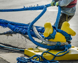 Dock worker pulls on heavy blue ropes of an ocean-going passenger ship are wrapped around a yellow mooring bollard on a city pier in the harbor. - 111203788