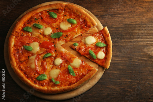 Foto op Canvas Pizzeria Sliced Margherita pizza on wooden background