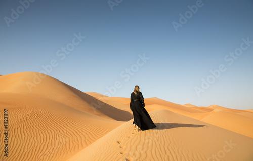 Foto op Canvas Abu Dhabi A woman in abaya in sanddunes in Liwa Desert, Aby Dhabi, UAE