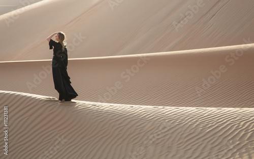 A woman in abaya in sand dunes in Liwa Desert, Abu Dhabi, UAE