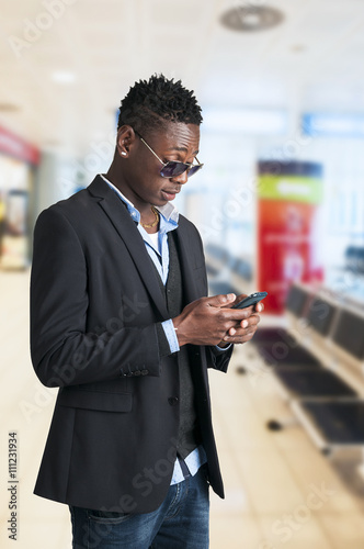 Young smart african american man sending message with mobile phone at airport lo Poster
