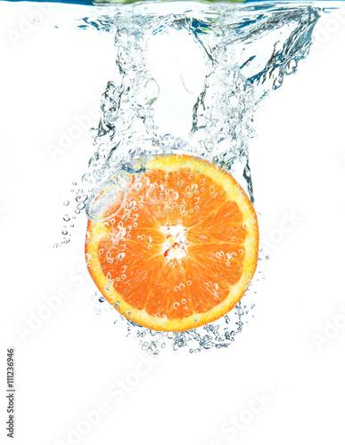fetta di arancia che cade in acqua