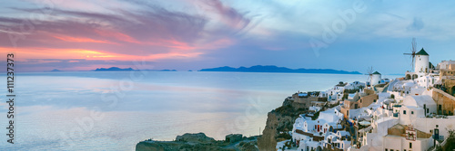 Panoramic famous view, Old Town of Oia or Ia on the island Santorini, white houses and windmills at sunset, Greece