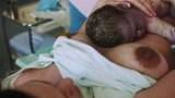 Woman hold newborn baby on stomach after birth give. Maternity hospital. Accoucheur gynecologists. Neonate