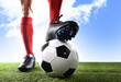 close up legs feet football player in red shocks and black shoes posing with ball standing on grass outdoors