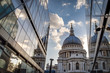 St Paul's cathedral seen from a narrow alley enclosed by glass buildings on a cloudy day in summer