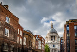 St Paul's cathedral seen from a narrow alley enclosed by brick buildings on a cloudy day in summer
