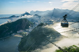 Bright misty view of the city skyline of Rio de Janeiro, Brazil with a Sugarloaf (Pao de Acucar) Mountain cable car passing in the foreground - 111288534